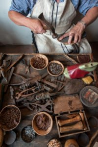The shoemaker repairs a shoe at his work bench 1