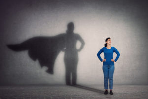 Brave woman keeps arms on hips, smiling confident, casting a superhero with cape shadow on the wall. Ambition and business success concept. Leadership hero power, motivation and inner strength symbol. 1